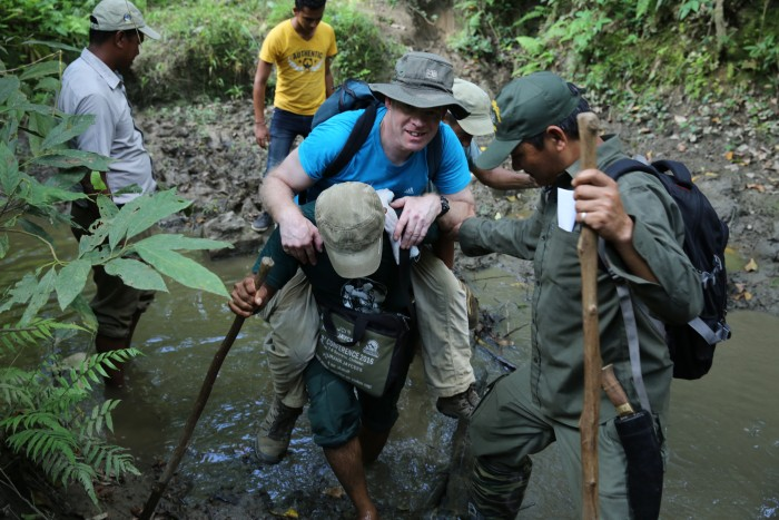 After the fall: national park ranger heroically carries Chris Cockel across a stream in the park's buffer zone.